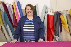 Более старая женщина в фабрике мебели подготавливает розовый материал для измерять и резать стоковые фото