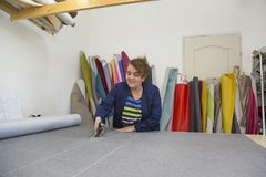Более старая женщина в фабрике мебели режет серый материал для софы стоковое изображение