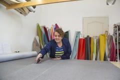 Более старая женщина в фабрике мебели режет серый материал для софы стоковые изображения rf
