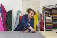 Более старая женщина в фабрике мебели режет серый материал для софы стоковые фотографии rf