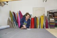 Более старая женщина в фабрике мебели режет серый материал для софы стоковые фото