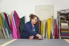 Более старая женщина в фабрике мебели режет серый материал для софы стоковое фото
