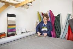 Более старая женщина в фабрике мебели режет серый материал для софы стоковое изображение rf