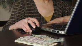 Более старая женщина использует ноутбук для того чтобы заработать деньги онлайн сток-видео