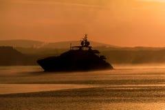 Большой крейсер мотора Silhouetted в тумане, звуке Плимута, южном Девоне стоковые изображения