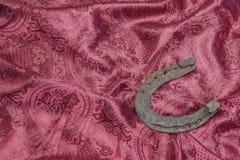 Ботинок лошади на красной предпосылке ткани стоковые фото