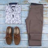 Ботинок, пояс, брюки и рубашка loafer Брауна изолированные на деревянной предпосылке Взгляд сверху стоковые изображения