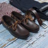 Ботинок, пояс, брюки и рубашка loafer Брауна изолированные на деревянной предпосылке Взгляд сверху стоковые фотографии rf