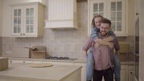 Бородатый человек носит милую женщину сидя на его назад в кухне Объятия женщины экономно расходуют и показывают ему направление с видеоматериал
