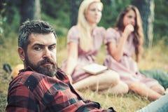 Бородатый человек с голубыми глазами тратя время с друзьями outdoors Человек крупного плана красивый в рубашке lumberjack лежа на стоковые фото
