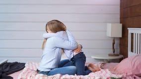 Босоногая девушка ребенка дает большое объятие ее матери сидя на кровати в съемке спальни дома внутренней полной сток-видео