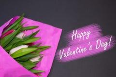 Валентайн дня счастливое s Букет свежих кнопок тюльпана в розовой бумаге на черной предпосылке Цветки пинка и белых лежат на табл стоковая фотография