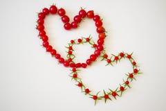 Два сердца из помидоров в слиянии. Two hearts of small red tomatoes in the merger Royalty Free Stock Images