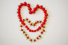 Два сердца из помидоров в слиянии. Two hearts of small red tomatoes in the merger Stock Image