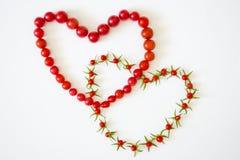 Два сердца из помидоров в слиянии. Two hearts of small red tomatoes in the merger Royalty Free Stock Photography