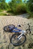 Велосипед лежа на песке Песок трудн для того чтобы ехать велосипедист никто, деревья на заднем плане Левая сторона велосипед стоковая фотография rf