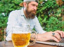 Вентилятор держал пари онлайн чемпионат пока сидите терраса outdoors с пивом Битник футбольного болельщика бородатый делает для т стоковое фото