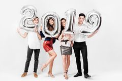 Веселые друзья 2 девушки и 2 парня одетых в стильных одеждах держат воздушные шары в форме 2019 на a стоковые изображения rf