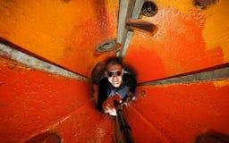 Веселый парень Selfie молодой со стеклами в отсеке торпедо подводной лодки Покрашенный в апельсине, концепция ограниченного космо стоковые фото