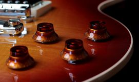 Весьма близкое поднимающее вверх фото управлений тома и тона электрической гитары стоковая фотография rf