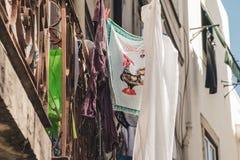 Ветошь с типичным петухом Португалии висит рядом с суша прачечной на балконе города Лиссабона стоковые изображения rf