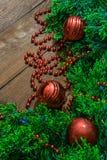 Вертикальное фото зеленых ветвей с ягодами обильно украшенными с игрушками для того чтобы украсить рождественскую елку на деревян стоковое изображение rf