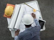 Верхнее viwe, инженеры в шлемах планируя новый проект на таблице Архитектор работая на светокопии стоковая фотография rf