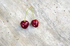 Верхняя съемка, конец вверх свежей сладкой вишни с падениями воды на светлой деревенской предпосылке деревянного стола, выборочно стоковая фотография rf