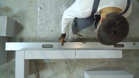 Верхняя часть вниз с взгляда построителя проверяя качество заново построенной стены с уровнем пузыря видеоматериал