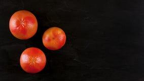 Верхняя часть вниз с взгляда, 3 розовых грейпфрута на черной мраморной доске, знамени с космосом для текста на правильной стороне стоковое фото rf