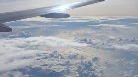 Взгляд из окна самолета с частью крыла и красивых облаков акции видеоматериалы