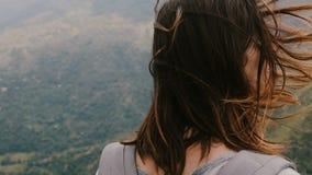 Взгляд конца-вверх задний снятый молодой туристской женщины с рюкзаком и ветром дуя в волосах наблюдая эпичный ландшафт горы видеоматериал