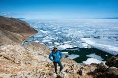 Взгляд над большим красивым Lake Baikal с ледяными полями плавая на воду с девушкой носит синий пиджак, Россию стоковые фотографии rf