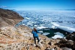 Взгляд над большим красивым Lake Baikal с ледяными полями плавая на воду с девушкой носит синий пиджак, Россию стоковая фотография rf