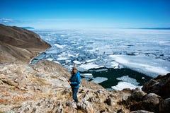 Взгляд над большим красивым Lake Baikal с ледяными полями плавая на воду с девушкой носит синий пиджак, Россию стоковое изображение