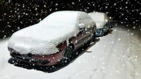 Взгляд низкого угла автомобилей припаркованных вдоль улицы вечером в зиме панорамно стоковое изображение
