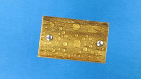 Взгляд сверху, вращение светлой деревянной планки с болтами утюга в дождевых каплях изолировано сток-видео