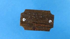 Взгляд сверху, вращение темной деревянной доски с болтами утюга в дождевых каплях изолировано сток-видео