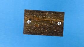 Взгляд сверху, вращение темной деревянной доски с болтами утюга в дождевых каплях изолировано акции видеоматериалы
