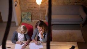Взгляд сверху крупного плана молодой кавказской мамы наблюдающ ее небольшим милым чертежом дочери Мать и тратить девушки их акции видеоматериалы