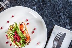 Взгляд сверху на сыре, авокадое и семгах тоста со сливками на белой плите стоковое фото