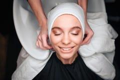 Взгляд сверху усмехаясь красивой женщины удовлетворяемой после профессиональной стирки и обрабатываемой волосы в салоне красоты э стоковое фото