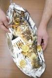 Взгляд сверху очень вкусных рыб, который сгорели к хрустящей корочке Мужские руки держа spatule для установки частей лимона стоковые фотографии rf