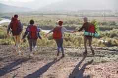 Взгляд от задней части 4 друзей хипстера с рюкзаком перемещения держа руки и бежать вперед к горе на заходе солнца стоковые изображения