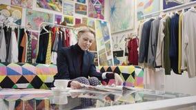 Взрослая женщина читает журнал в магазине одежды видеоматериал