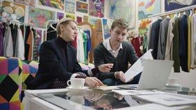 Взрослая коммерсантка и ее молодой мужской деловой партнер обсуждают их будущий проект таблицей сток-видео