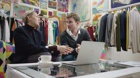 Взрослая коммерсантка и ее молодой мужской работник обсуждая проект дела путем использование ноутбука видеоматериал
