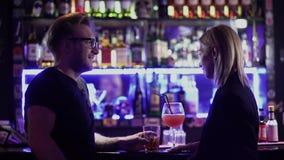 Взрослые коктейли напитка пар на счетчике бара Человек в стеклах и белокурой женщине говоря на диско Иметь потеху на сток-видео