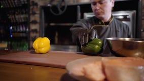 Взрослый шеф-повар кладет на болгарский перец таблицы желтый и зеленый, перец красного chili и конец лимона вверх Запачканная пли сток-видео