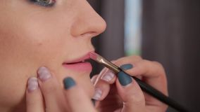 Визажист используя щетку для губной помады применения на женщине губ красивой Конец вверх по лоску губы применения на губах видеоматериал